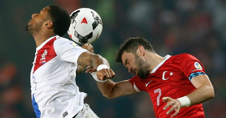 15.out.2013 - Jeremain Lens (e), da Holanda, disputa jogada pelo alto com Gökhan Gönül, da Turquia, em partida pelas eliminatórias da Copa do Mundo-2014