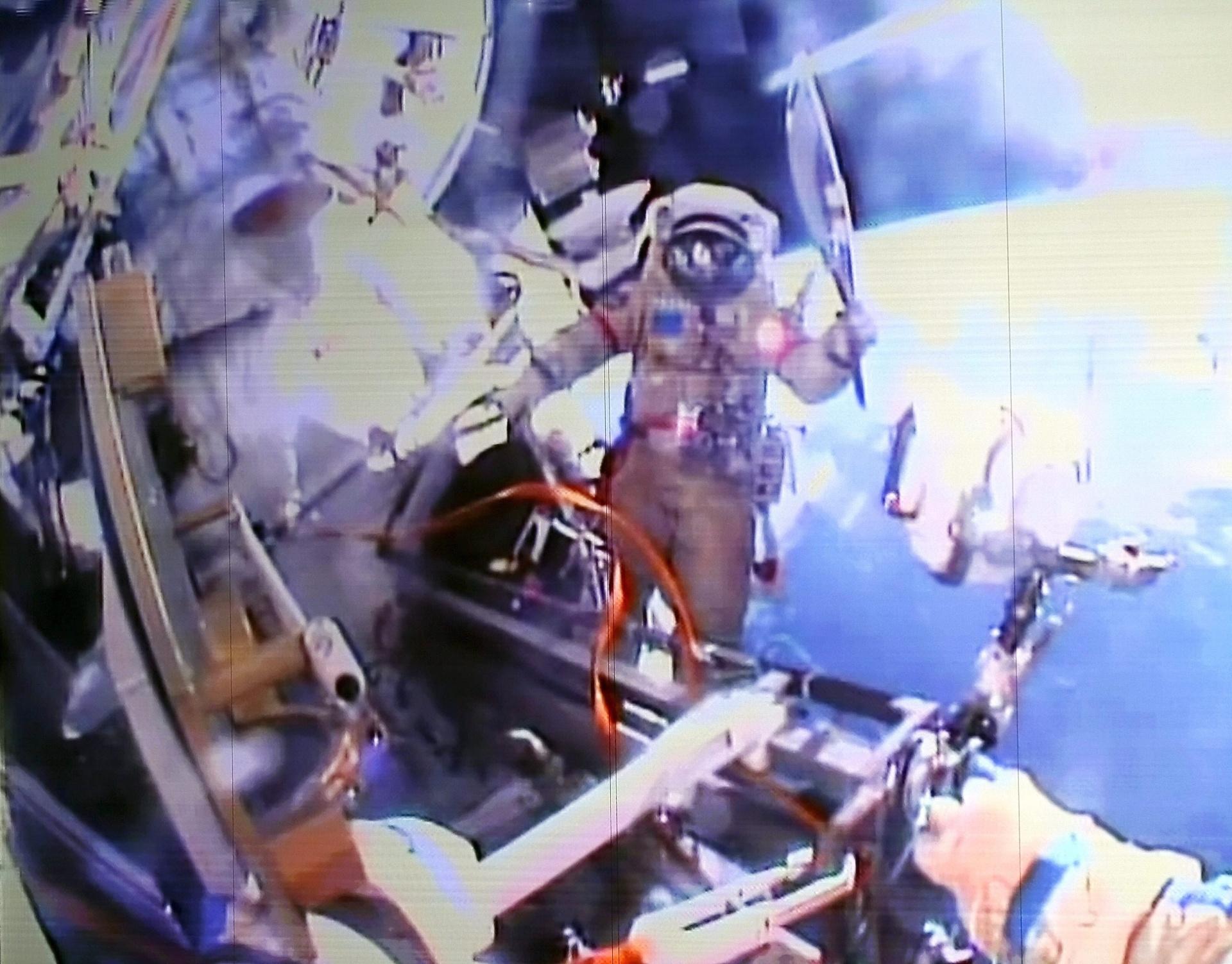 09.nov.2013 - Do lado de fora da Estação Espacial, o cosmonauta russo Oleg Kotov segura a Tocha Olímpica de Inverno