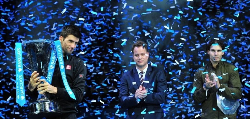 11.nov.2013 - Rafael Nadal aplaude enquanto Novak Djokovic ergue o troféu de campeão das Finais da ATP
