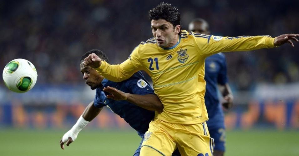 15.nov.2013 - Edmar (dir.), brasileiro naturalizado ucraniano, briga pela bola com o francês Evra em partida da repescagem para a Copa do Mundo