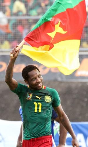 17.nov.2013  - Jean Makoun carrega uma bandeira de Camarões pelo campo após a goleada por 4 a 1 sobre a Tunísia; resultado classificou os Leões Indomáveis para a Copa-2014