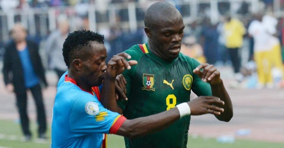 16.jun.2013 - Joseph Najeng (d), de Camarões, sofre marcação cerrada de Issama, da República Democrática do Congo, durante partida das eliminatórias da Copa-2014; jogo terminou empatado sem gols
