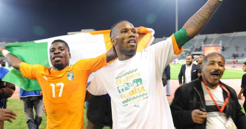 16.nov.2013 - Serge Aurier (e) e Didier Drogba comemoram a classificação da Costa do Marfim para a Copa-2014 após o empate por 1 a 1 com Senegal