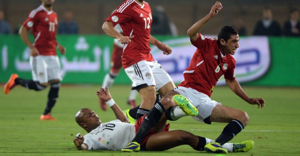 19.nov.2013 - Ayew, de Gana, dá carrinho para tirar a bola de Rabia, do Egito; apesar da derrota por 2 a 1, ganenses se classificaram para a Copa-2014