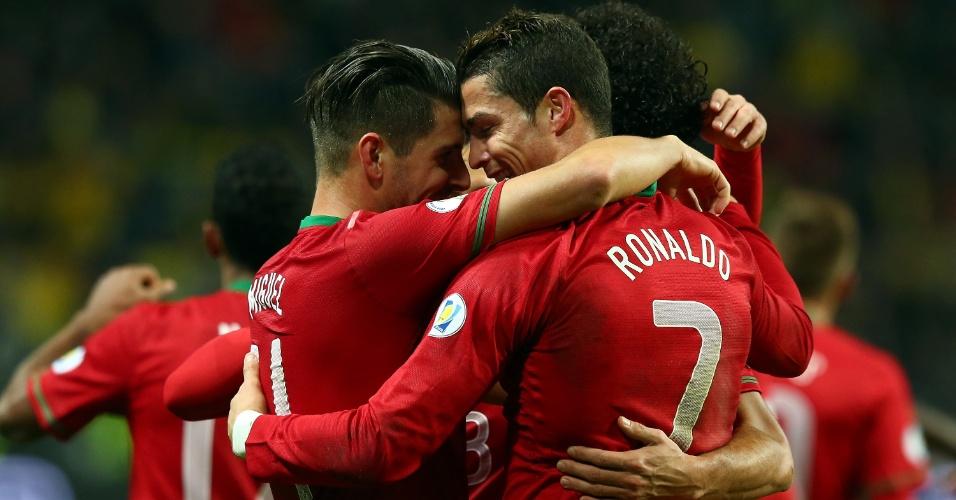 19.nov.2013 - Cristiano Ronaldo abraça o companheiro Miguel Veloso após marcar para Portugal na partida contra a Suécia; vitória por 3 a 2 classificou os portugueses para a Copa-2014