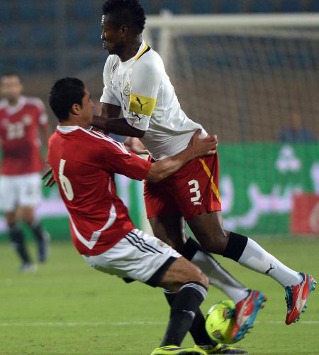 19.nov.2013 - Rabia (à esquerda), do Egito, disputa bola com Asamoah Gyan, de Gana; mesmo com a derrota por 2 a 1, ganenses se classificaram para a Copa-2014