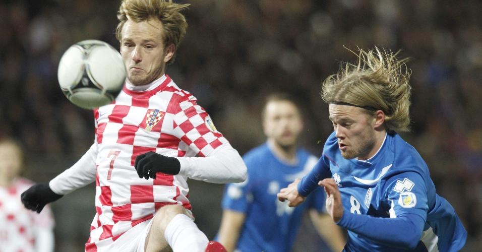15.nov.2013 - Observado por Birkir Bjärnason (d), da Islândia, Ivan Rakitic domina a bola no duelo de ida da repescagem europeia para a Copa-2014; jogo terminou empatado por 0 a 0