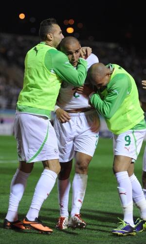 19.nov.2013 - Madjid Bougherra (c) é abraçado por Hassan Yebda e Rafik Djebbour após marcar o gol da vitória por 1 a 0 da Argélia sobre Burkina Fasso; resultado classificou os argelinos para a Copa do Mundo-2014