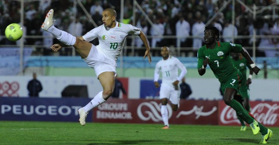 19.nov.2013 - Observado por Florent Rouamba (d), de Burkina Fasso, Sofiane Feghouli, da Argélia, faz jogada acrobática; argelinos venceram por 1 a 0 e se classificaram para a Copa-2014