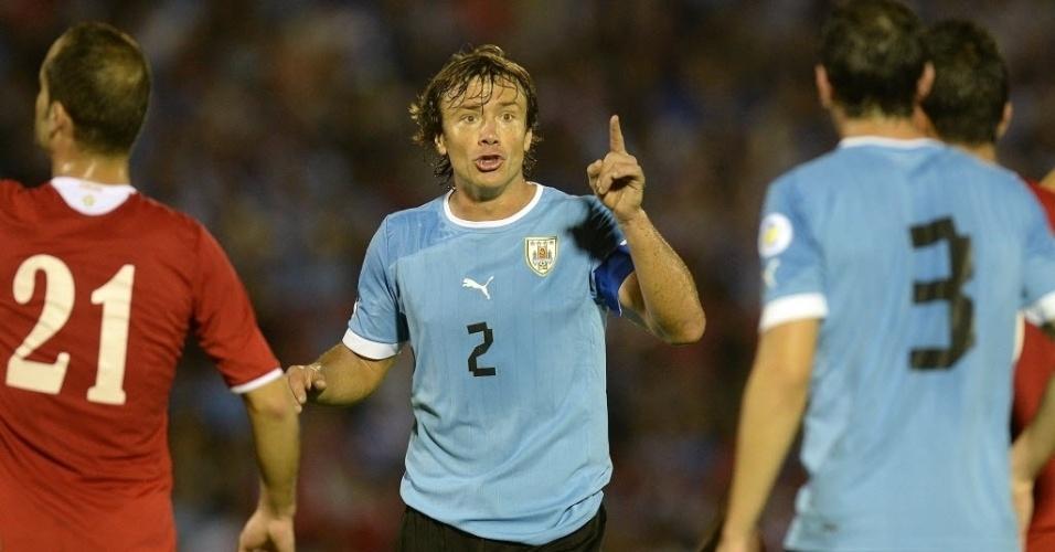 20.nov.2013 - Lugano conversa com o zagueiro Gódin no empate do Uruguai com a Jordânia por 0 a 0; resultado confirmou a classificação dos uruguaios para a Copa-2014
