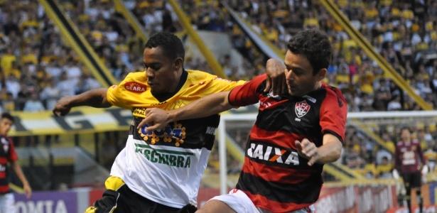 Lins, atacante do Criciúma, e Juan, lateral do Vitória, disputam a bola próxima à linha lateral