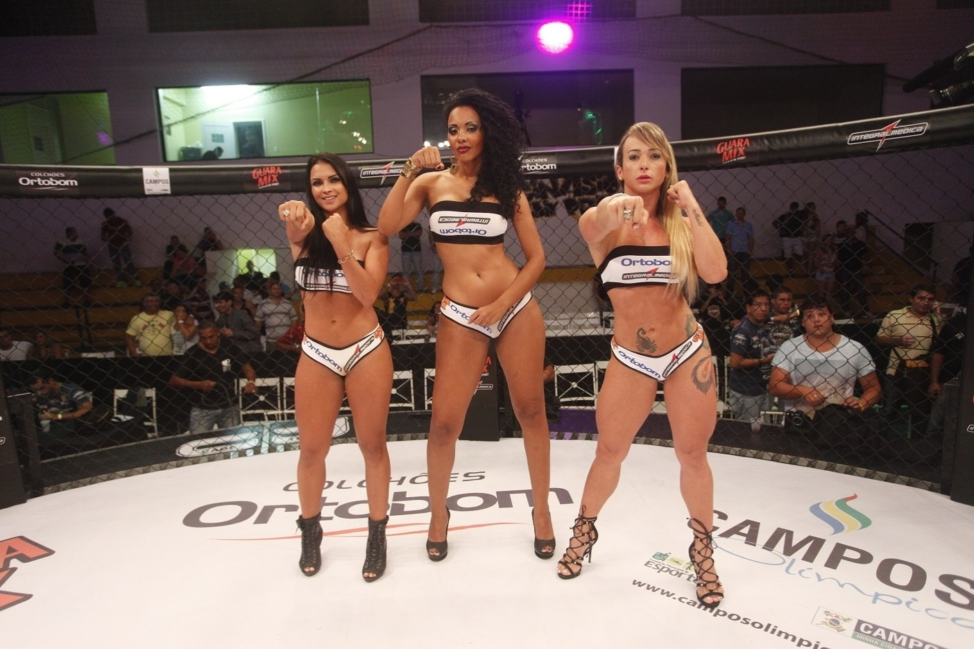 Ex-BBB Aline (centro), que esteve na 13ª edição do programa, trabalha como ring girl do Jungle Fight e ergue as plaquinhas de round no evento em Campos (RJ)