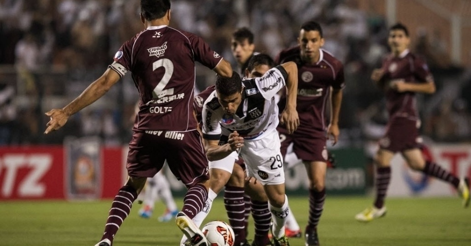 04.dez.2013 - Atacante Leonardo, da Ponte Preta, é marcado por vários jogadores do Lanús em lance da final da Copa Sul-Americana