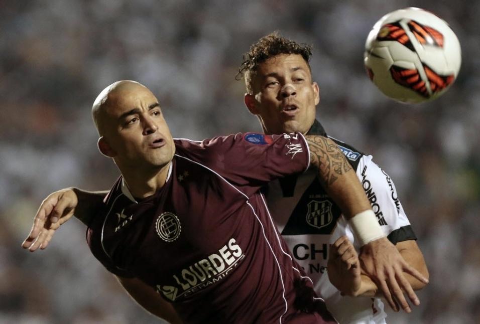 04.dez.2013 - Volante Baraka (dir.), da Ponte Preta, disputa a bola com o argentino Santiago Silva, do Lanús, durante a final da Sul-Americana
