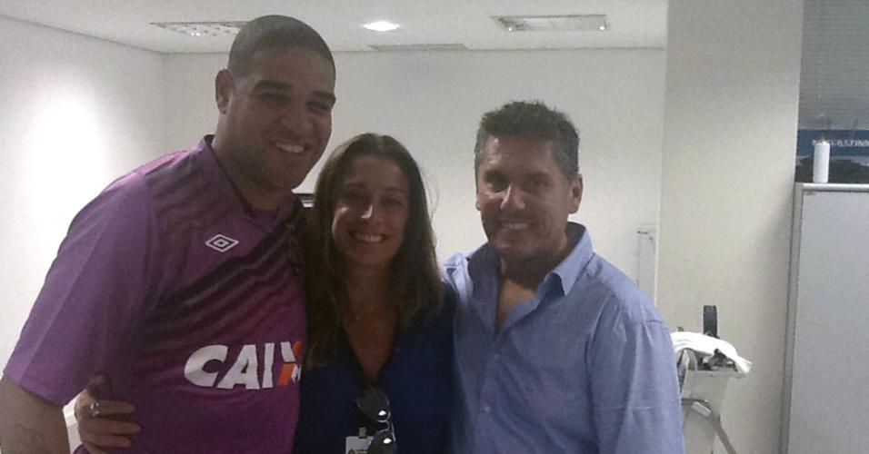 Adriano (esq.) aparece com a camisa de treino do Atlético-PR, acompanhado da assessora Renata Battaglia e do seu empresário Luiz Claudio Menezes (dir.)