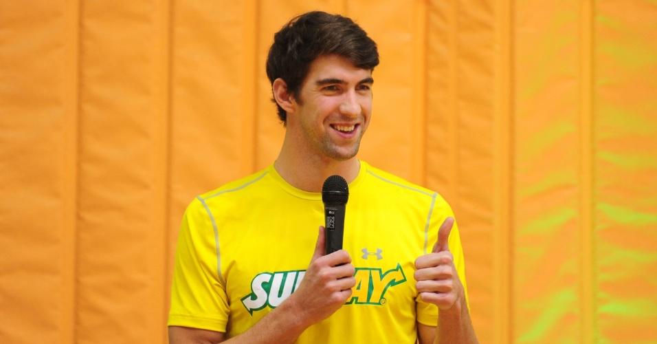 Ex-nadador Michael Phelps acena durante evento com crianças em São Paulo