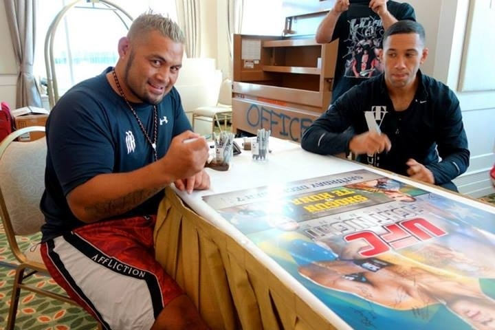 Mark Hunt (à esq.) dá seu autógrafo no poster oficial do UFC: Pezão x Hunt