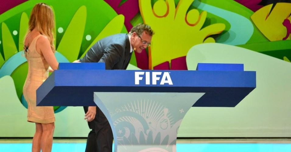 06.dez.2013 - Jérôme Valcke se abaixa para pegar uma bolinha que caiu no chão durante o sorteio dos grupos da Copa do Mundo
