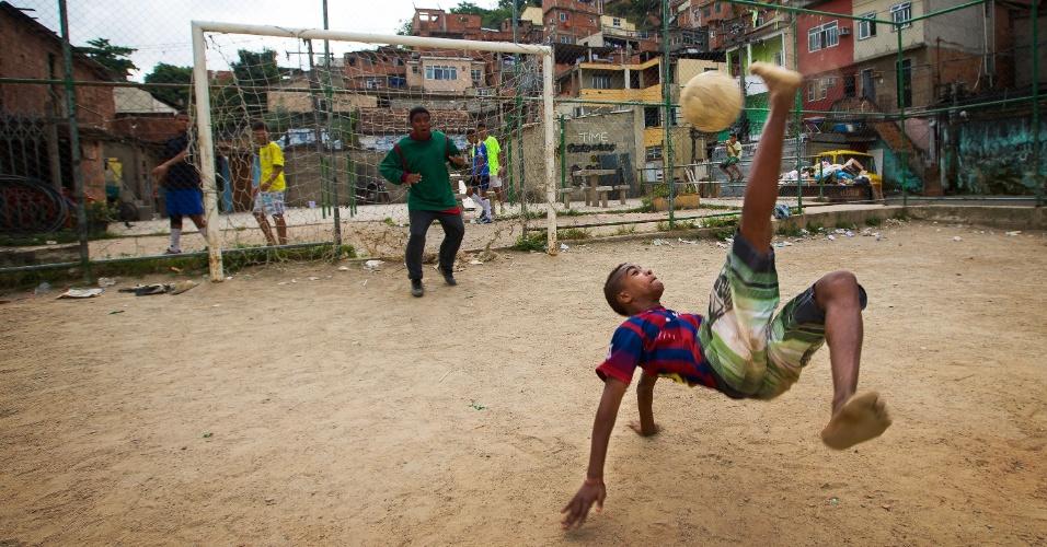 26.out.2013 - Garotos jogam futebol em campo no meio da favela Morro dos Macacos, no Rio de Janeiro