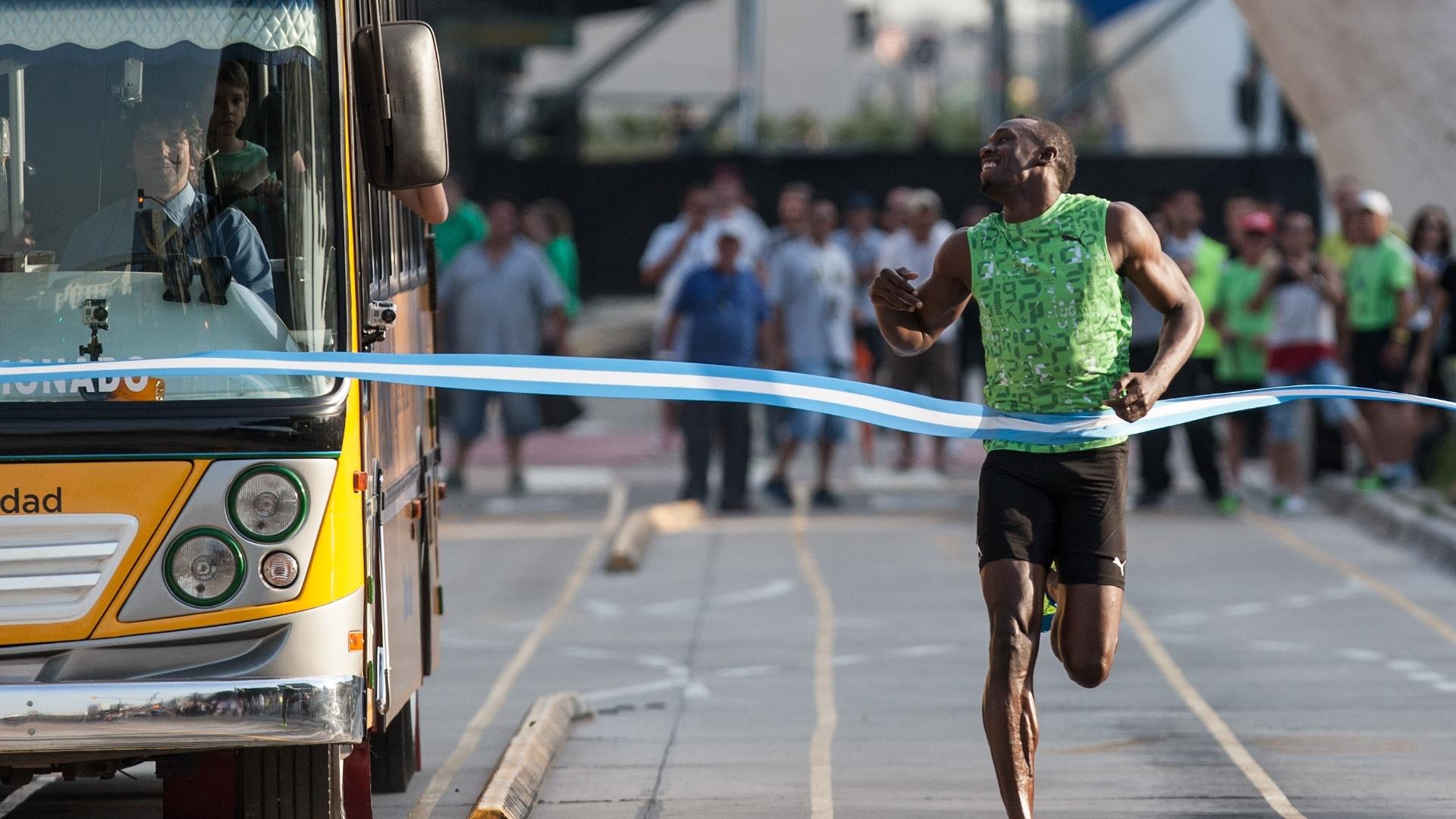 14.dez.2013 - Bolt cruza a linha de chegada antes de ônibus em desafio de 100 m na Argentina