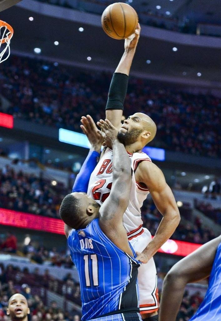 16.dez.2013 - Taj Gibson, do Chicafgo Bulls, enterra por cima de Glen Davis, do Orlando Magic; apesar do belo lance, os Bulls perderam em casa por 83 a 82