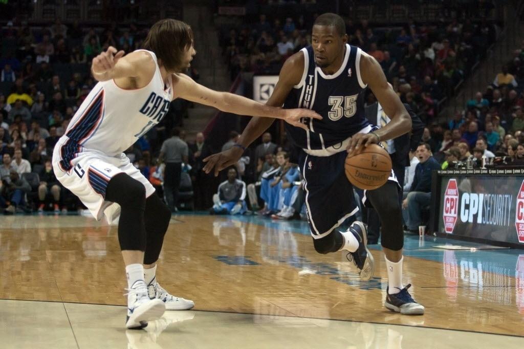 28.dez.2013 - Kevin Durant (dir.) tenta passar pela marcação de Josh McRoberts durante a vitória do Oklahoma City Thunder sobre o Charlotte Bobcats