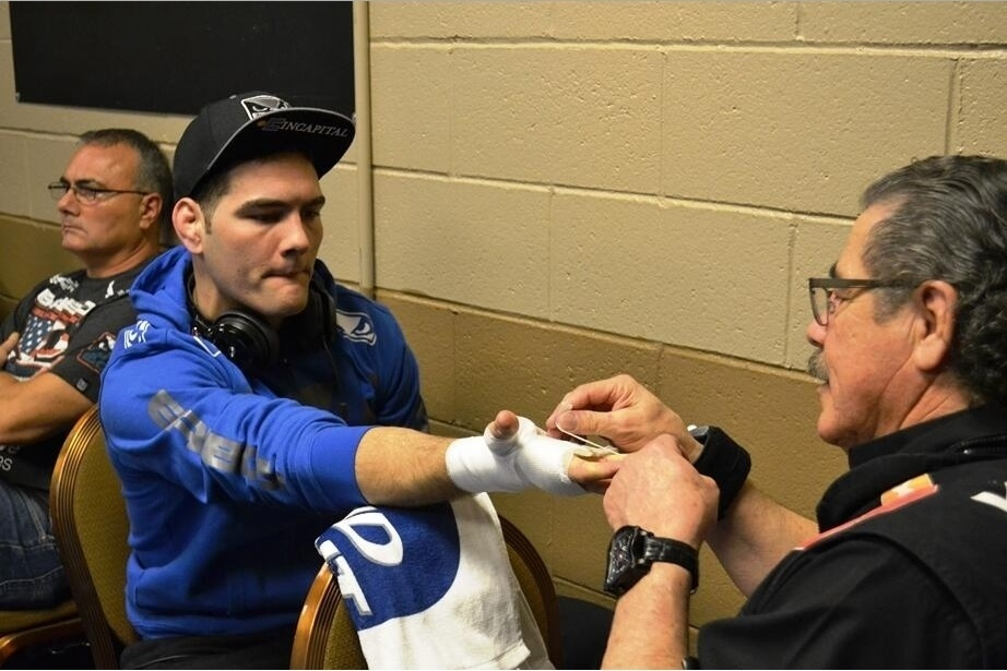 28.dez.2013 - Chris Weidman observa enquanto sua bandagem é feita pelo cut man do UFC