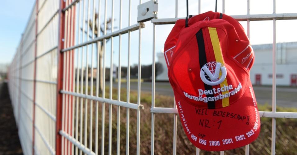 30.dez.2013 - Fã deixa um boné pendurado na cerca do kart de Michael Schumacher, na Alemanha.