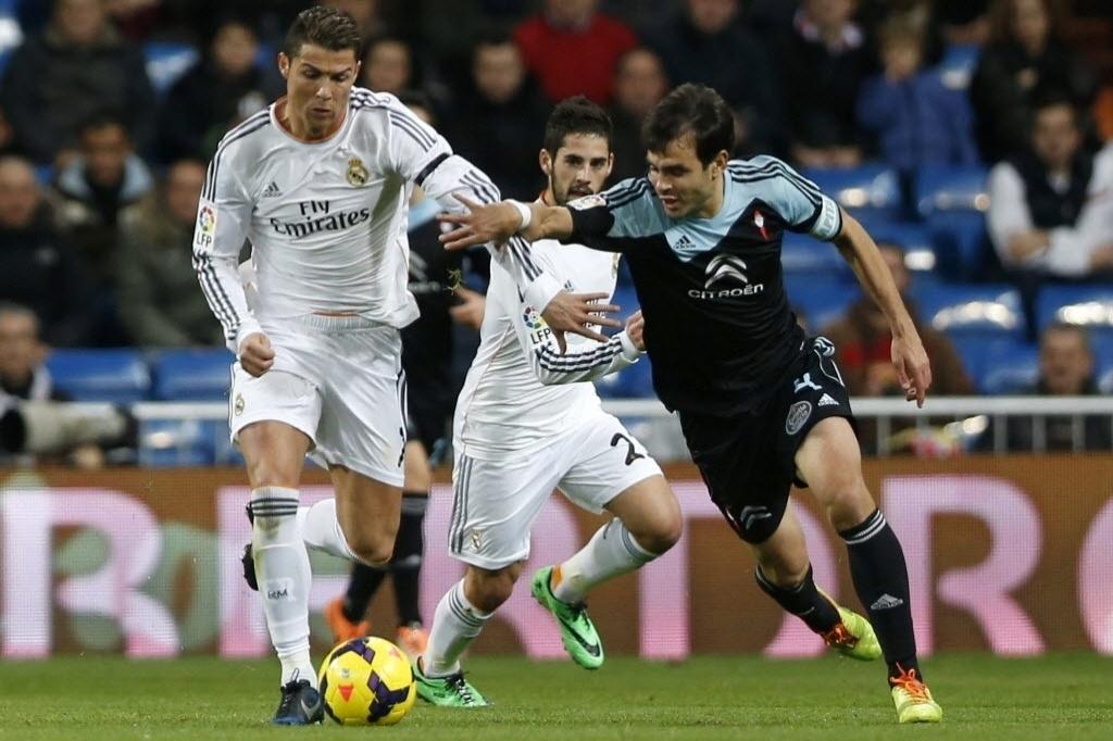 06.jan.2014 - Oubiña, do Celta, tenta segurar Cristiano Ronaldo na partida entre Real Madrid e Celta, pelo Campeonato Espanhol