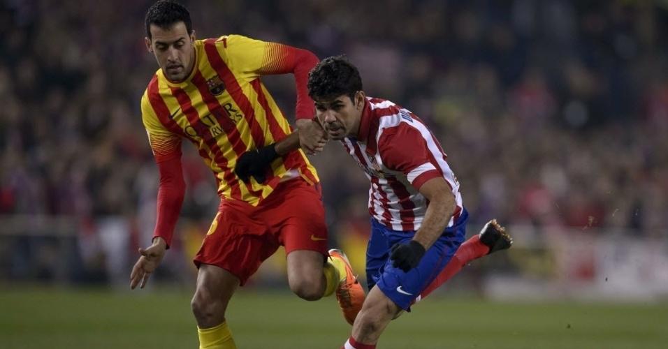 11. jan. 2014 - Diego Costa tenta ficar com a bola para o Atlético de Madri em duelo contra Busquets, do Barcelona