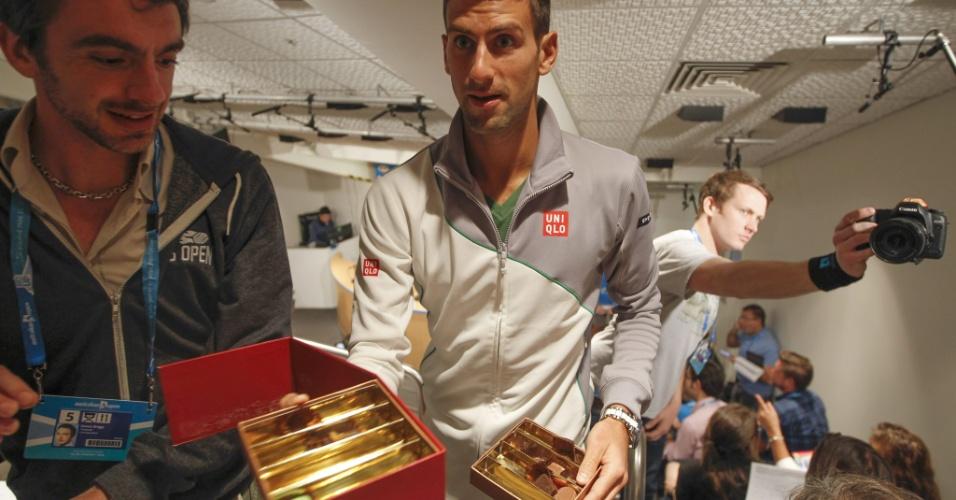 12.jan.2014 - Novak Djokovic distribui chocolates na primeira coletiva de imprensa do Aberto da Austrália, em Melbourne