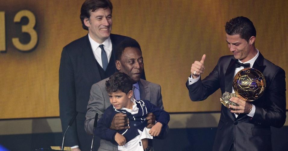 13.jan.2014 - Cristiano Ronaldo recebe a Bola de Ouro de 2013 com seu filho segurado por pelé no placo