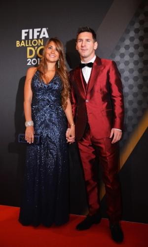 13.jan.2014 - Vestido com um terno vermelho, atacante argentino Lionel Messi posa com a mulher Antonella Roccuzzo