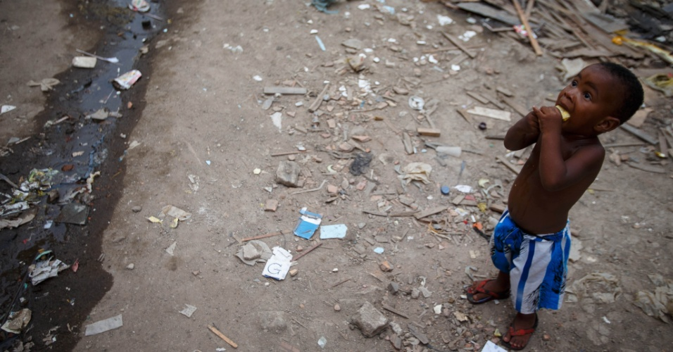 Criança come laranja na comunidade Metrô-Mangueira, que deve ser extinta ainda antes da Copa