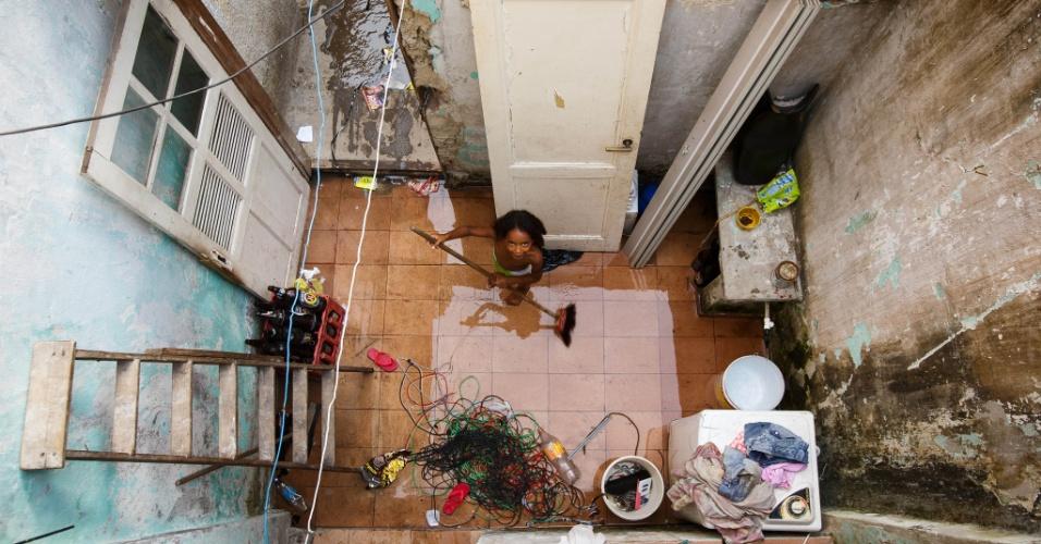 Criança limpa pátio em moradia na comunidade Metrô-Mangueira, na zona norte do Rio