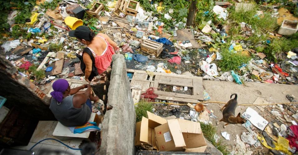Mulheres em meio aos destroços de moradias destruídas em remoção na comunidade Metrô-Mangueira