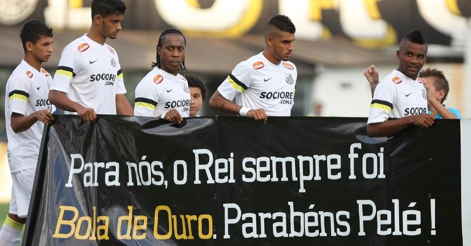 18.jan.2014 - Jogadores do Santos entram com faixa em homenagem a Pelé e a bola de ouro recebida pela Fifa