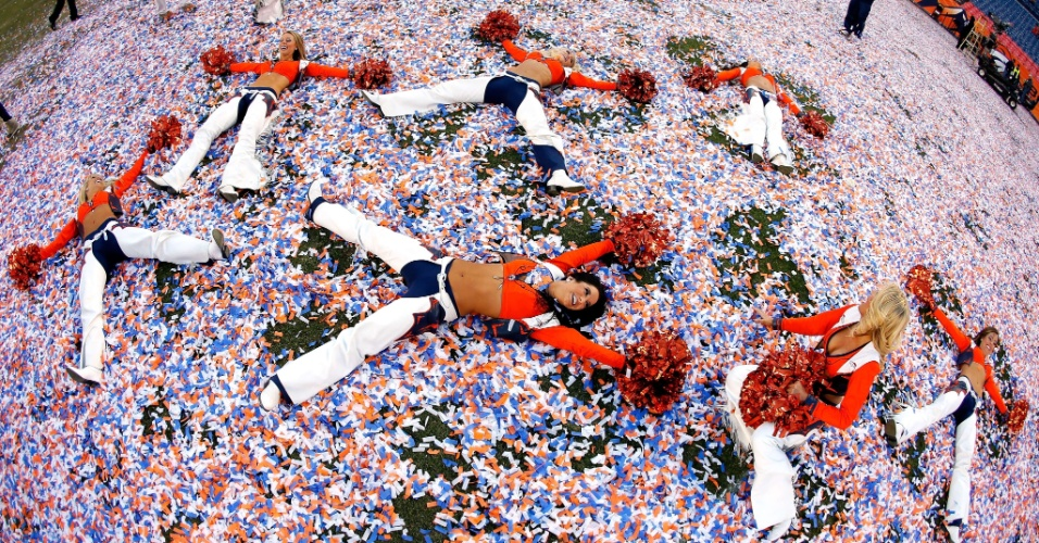 19.jan.2014 - Cheerleaders do Denver Broncos brincam no gramado repleto de papéis picados após título da conferência americana
