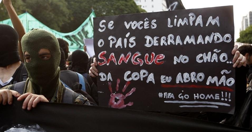 25.jan.2014 - Manifestantes carregam cartazes contra a realização da Copa do Mundo no Brasil em protesto na avenida Paulista