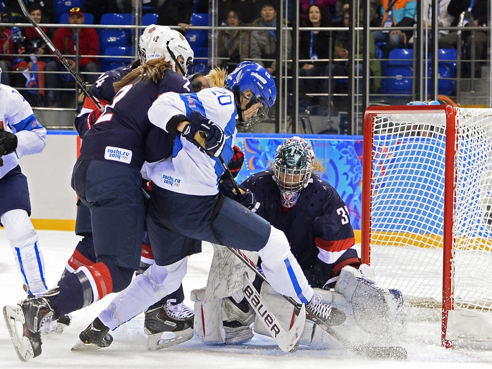 08.02.2014 - Finlandesa Saija Tarkki (branco) é empurrada por rivais americanas tentando evitar gol