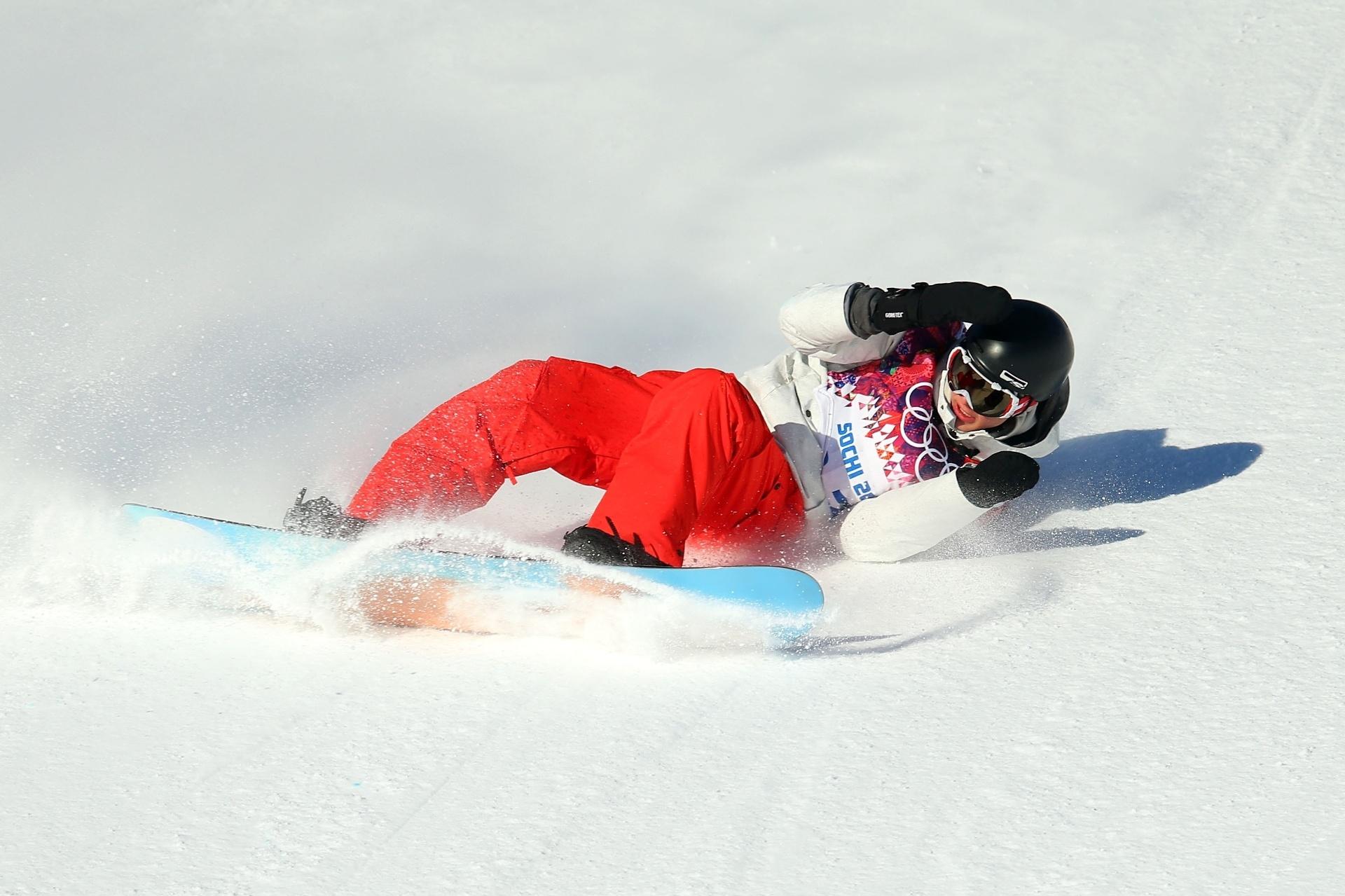 08.02.2014 - Suíço Lucien Koch tenta proteger o rosto ao cair na semifinal do Snowboard Slopestyle