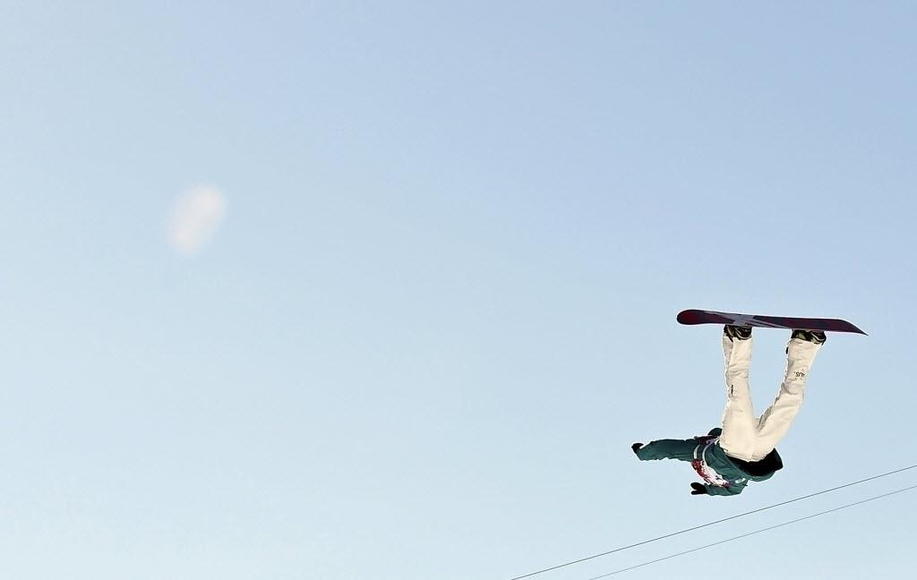 09.02.2014 - Scotty James, da Austrália, fica de ponta cabeça e ergue os braços na prova de snowboard slopestyle