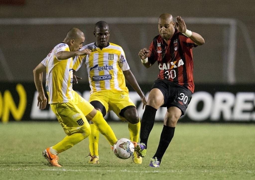 13.fev.2014 - Adriano disputa a bola com jogador do The Strongest na sua estreia pelo Atlético-PR