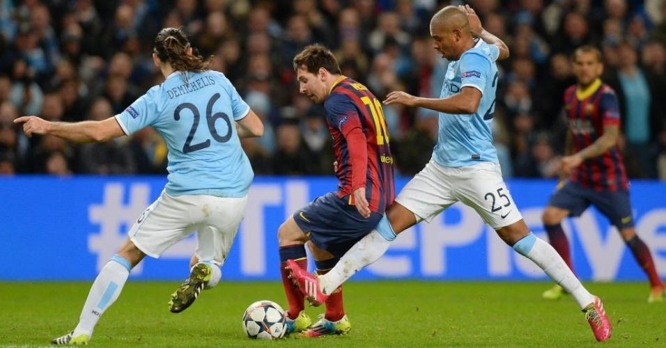 18.fev.2014 - Messi encara a marcação de dois jogadores do Manchester City, pelas oitavas de final da Liga dos Campeões da Europa