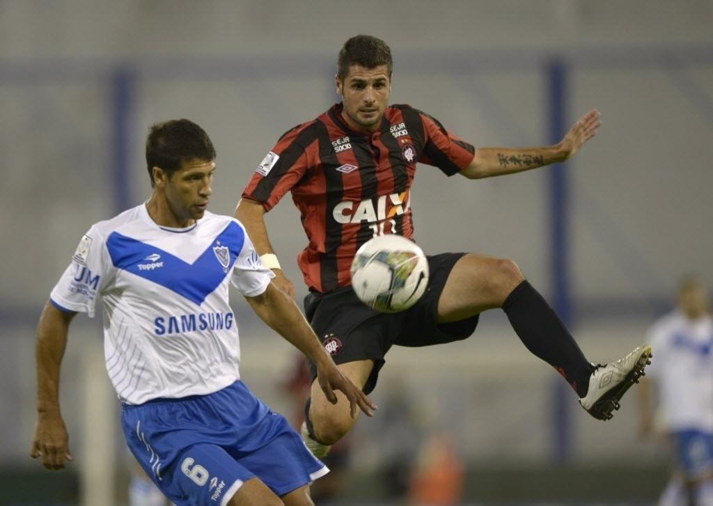 25.fev.2014 - Mérida, do Atlético-PR, marca o ex-zagueiro corintiano Sebá Dominguez, hoje no Vélez Sarsfield