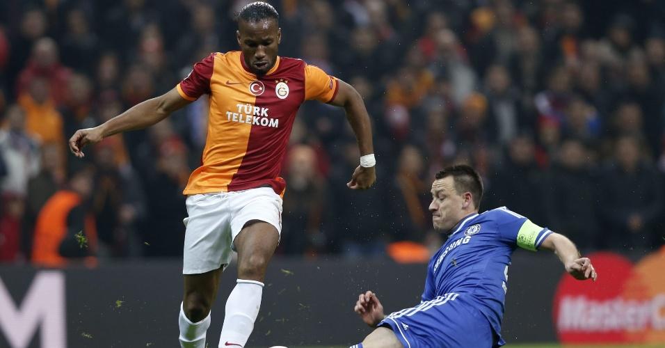 26.fev.2014 - Atacante Drogba, do Galatasaray, recebe carrinho do zagueiro John Terry, do Chelsea, em jogo de ida das oitavas de final da Liga dos Campeões