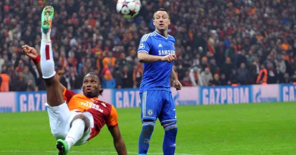 26.fev.2014 - Marfinense Didier Drogba, do Galatasaray, dá bicicleta enquanto zagueiro John Terry, do Chelsea, apenas observa em duelo pelas oitavas de final da Liga dos Campeões