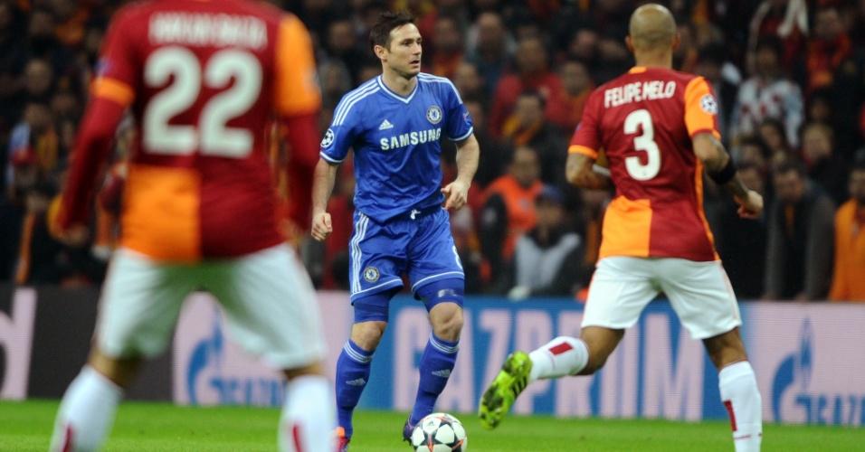 26.fev.2014 - Meia Lampard, do Chelsea, domina a bola enquanto é observado pelo brasileiro Felipe Melo, do Galatasaray, em jogo pela Liga dos Campeões
