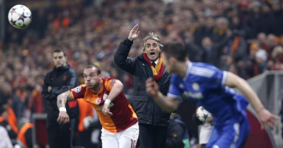 26.fev.2014 - Sneijder cobra lateral para o Galatasaray enquanto o técnico Roberto Mancini incentiva equipe turca ao fundo em duelo contra o Chelsea, pela Champions