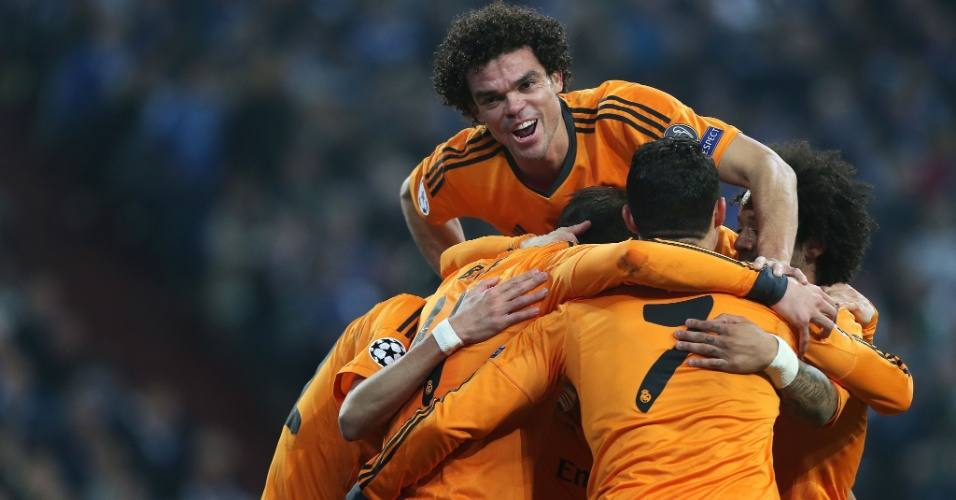 26.fev.2014 - Zagueiro luso-brasileiro Pepe pula sobre companheiros de Real Madrid para comemorar gol espanhol em goleada sobre o Schalke 04, na Alemanha, pela Champions